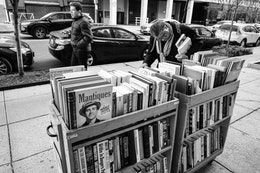 A woman looking at books for sale on the sidewalk outside Second Story Books in Dupont Circle.