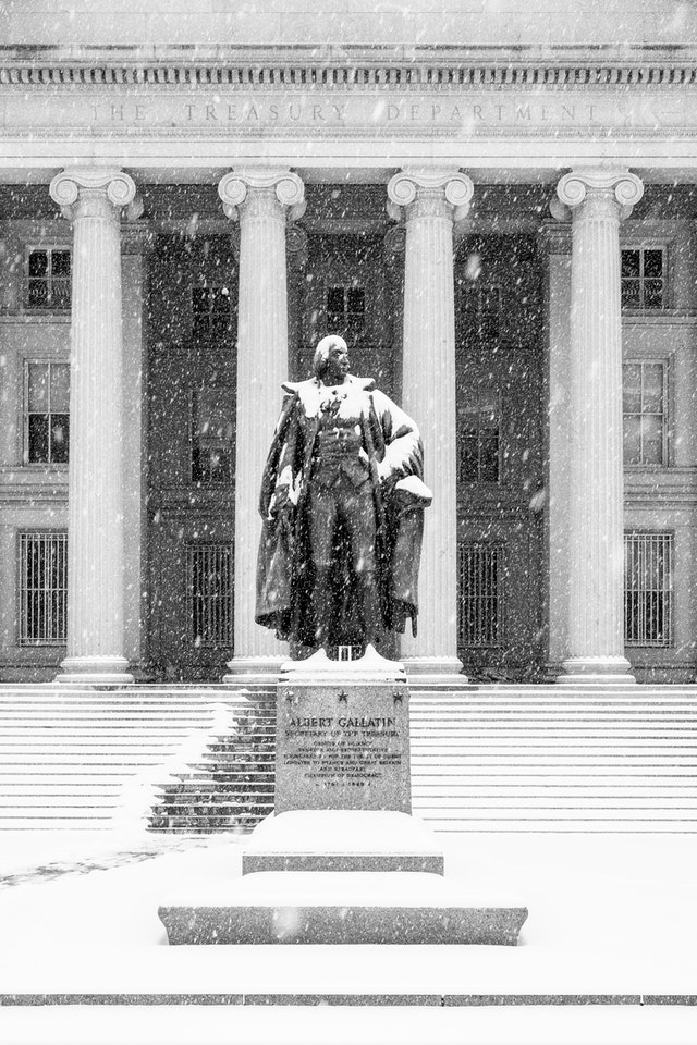Snow-covered statue of Albert Gallatin in front of the Treasury Department.
