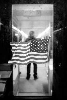 An American flag on the window of the door at the end of a Metro car, with a man standing on the next car in the background.