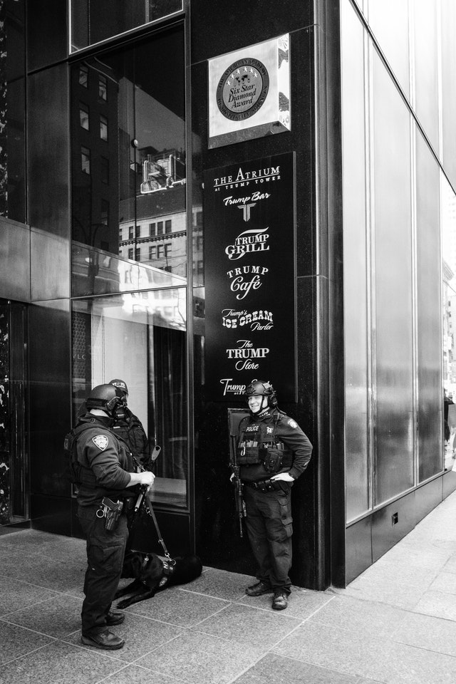 Three NYPD officers and a dog standing outside Trump Tower in New York City