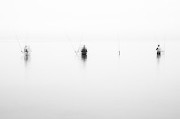 Three fishermen standing waist-deep in Lake Michigan, in deep fog.