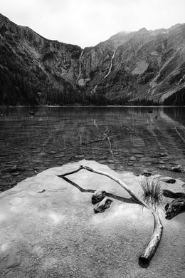 Avalanche Lake. In the foreground, a few rocks and a curved log half submerged in the lake's water. In the background, two waterfalls running down the sides of the mountain at the end of the lake.