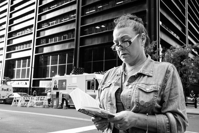 A woman reading a book while walking along Broadway in New York's Financial District.