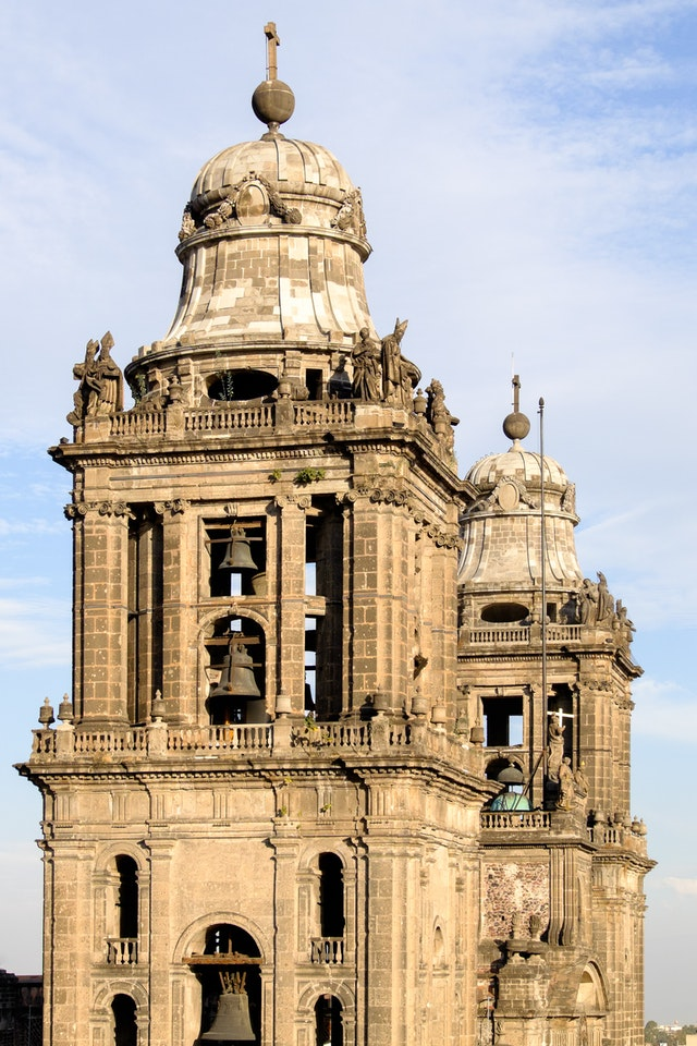 The bell towers of the Catedral Metropolitana in Mexico City, bathed in golden sunset light.