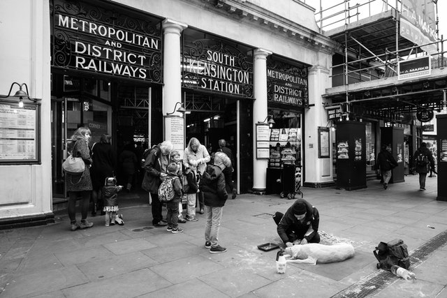 A man sculpting a dog out of sand in front of the South Kensington Station in London.