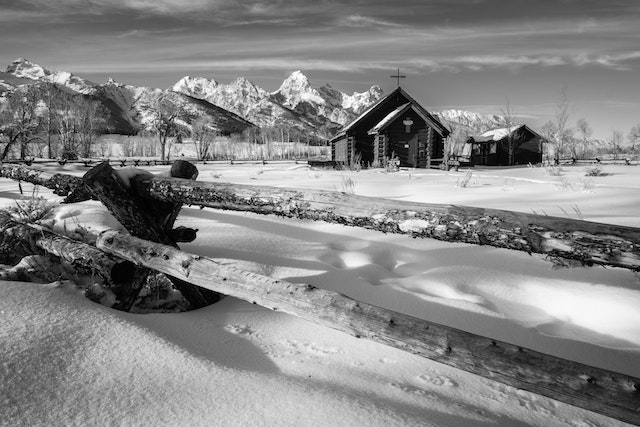 The Chapel of the Transfiguration seen behind a wooden fence in winter, with the Tetons in the background.