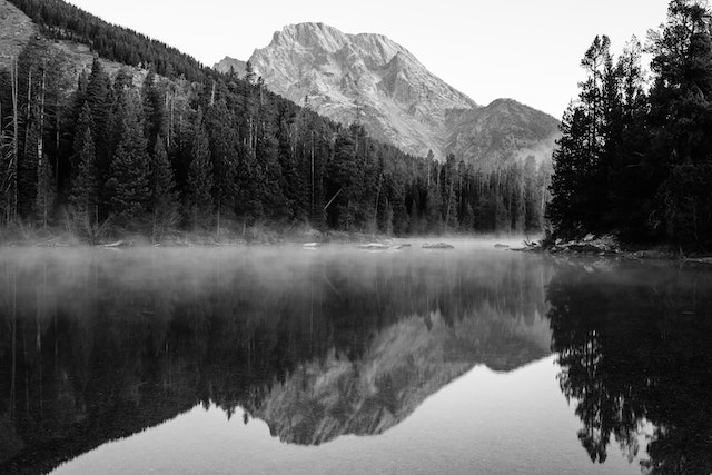 Mist floating over the surface of String Lake at dawn. Mount Moran can be seen in the background.