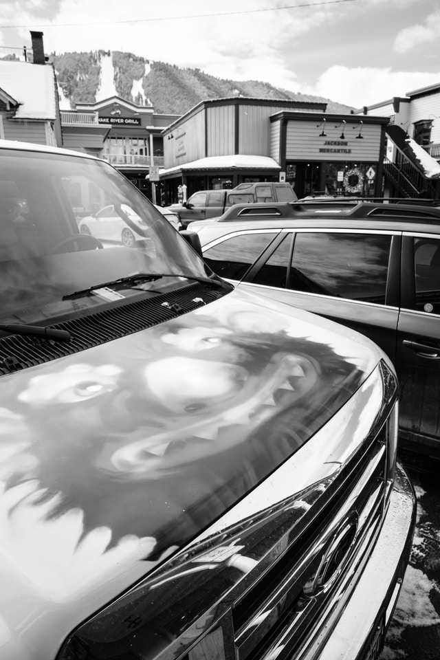 A white van parked in Jackson, Wyoming, with a grotesque clown monster thing painted on the hood.