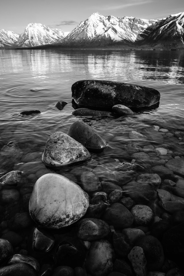A series of boulders in the waters of Jackson Lake. In the background, the snow-covered Teton Range.