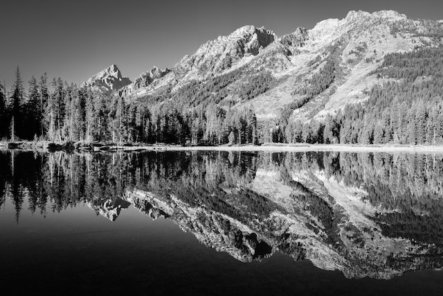 The Teton range, including Symmetry Spire and Teewinot Mountain, seen reflected on the surface of String Lake.