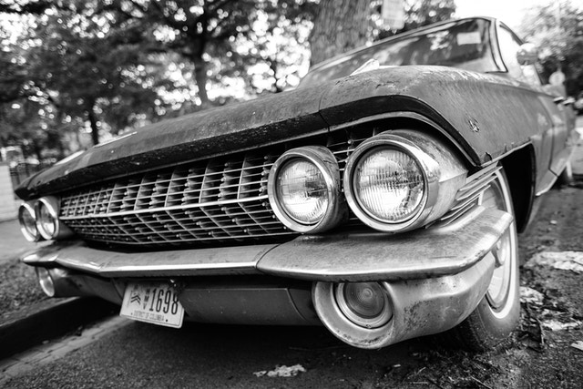 Front left corner of a rusted 1960s Cadillac de Ville parked on 9th Street & K Street NE in Washington, DC.