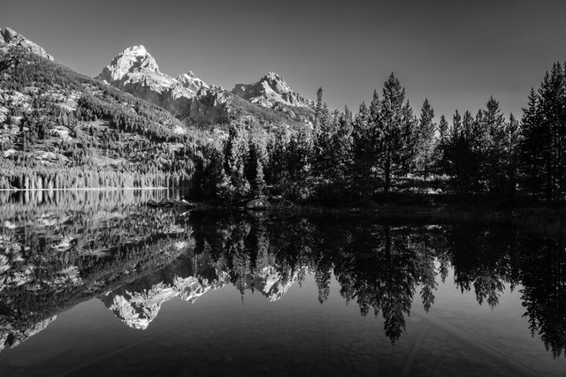 Grand Teton and Teewinot Mountain, reflected in the waters of Taggart Lake.