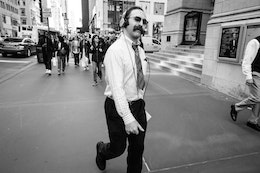 A man with a very bushy mustache wearing sunglasses and headphones smiling at my camera as he walks along Fifth Avenue.