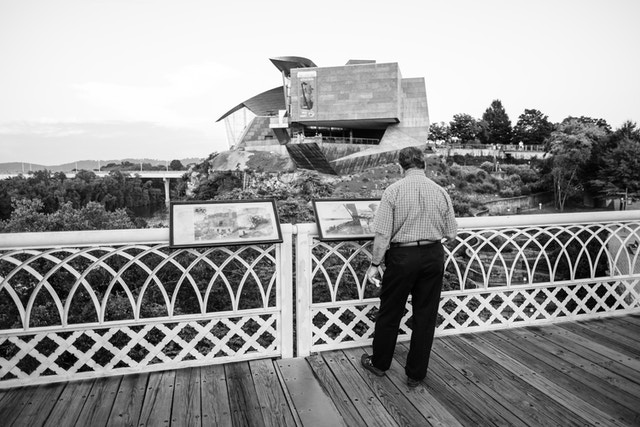 A man looking at information signs on the Walnut Street Bridge in Chattanooga, in front of the Hunter Museum.