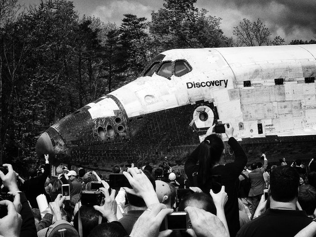 People taking photos of the Space Shuttle Discovery as it arrives on the tarmac.