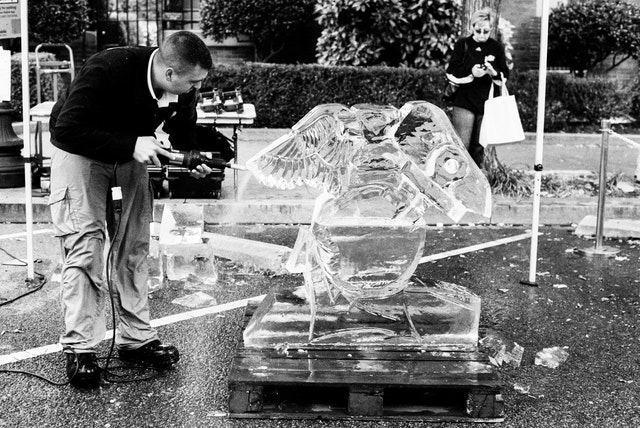 A Marine sculpting the United States Marine Corps Globe & Anchor on a block of ice.