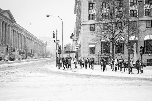 Tourists waiting to cross a snow-covered Pennsylvania Avenue at 15th street.