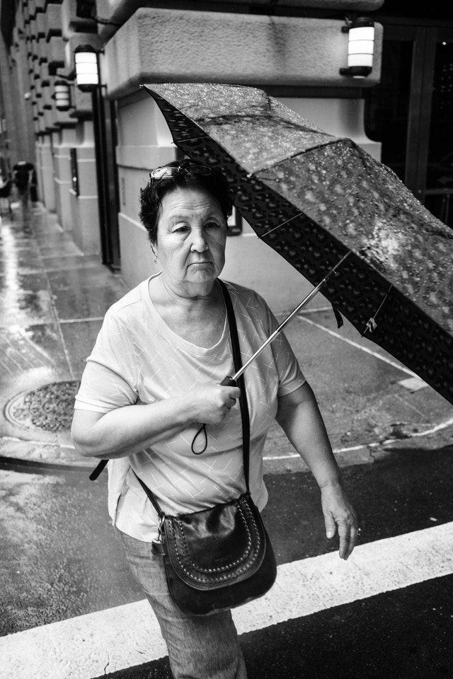 A woman carrying an umbrella in the rain, on the intersection of William & Pine streets in New York City.