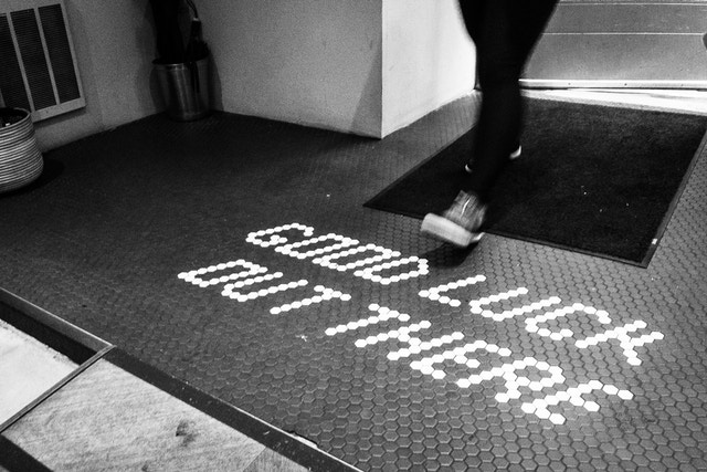 """A person walking into Black Fox Coffee, where """"good luck out there"""" is written in the tiles on the floor."""