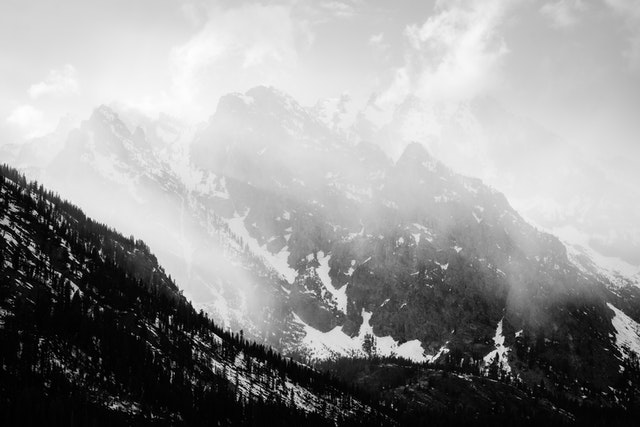 A spring storm clearing over Cascade Canyon, with sunlit clouds moving past Storm Point, Symmetry Spire, and Mount Saint John.