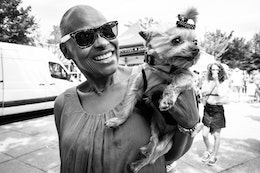 A little dog called Teacup, being held by her owner at Eastern Market.