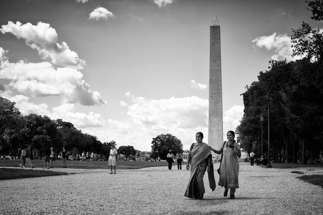 Two women walking on the National Mall in front of the Washington Monument.
