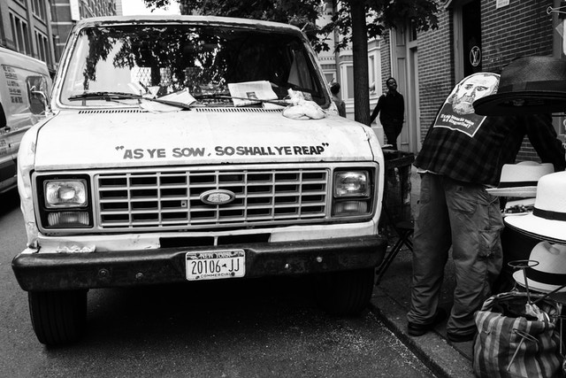 """An old Ford van in Soho, which has """"as ye sow, so shall ye reap"""" written on the hood."""