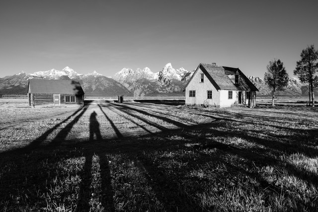 The pink stucco house and one of the log cabins at Mormon Row in Grand Teton National Park, with the Tetons in the background. My shadow is between the two structures.