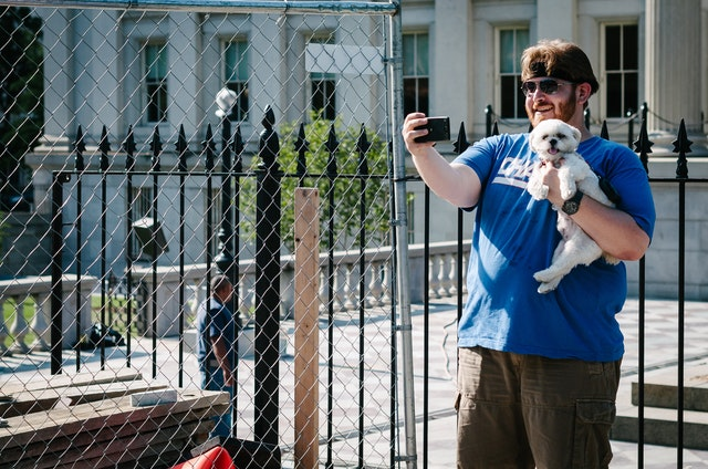 A man in a blue shirt and cargo shorts holding up a small white dog and taking a selfie in front of the Treasury Building in Washington, DC.