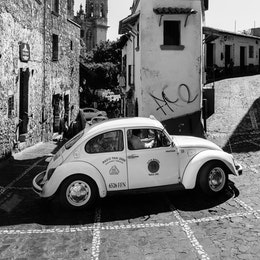 A Volkswagen Beetle taxing turning on a tight street in Taxco.