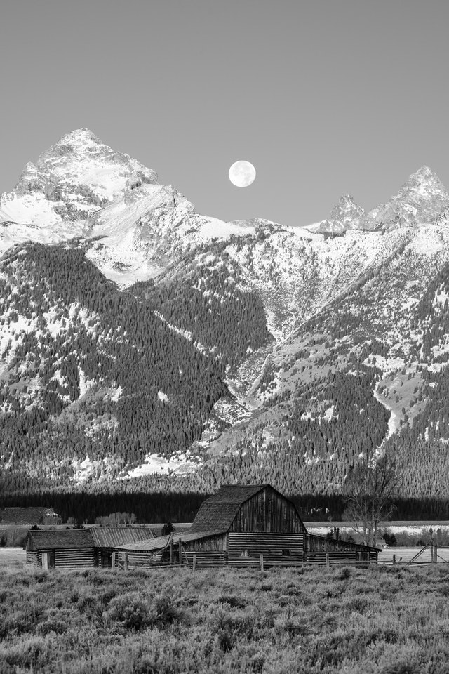 The John Moulton barn at Mormon Row. In the background, the Moon setting behing the Tetons.