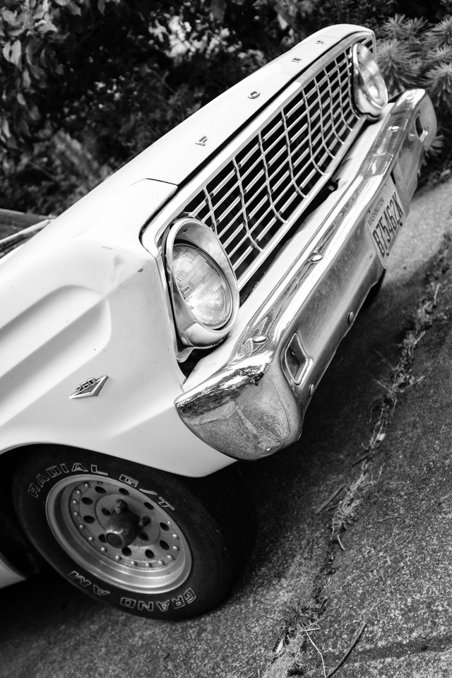 The front grille of a cool white 1964 Ford Ranchero parked in a driveway on Capitol Hill.