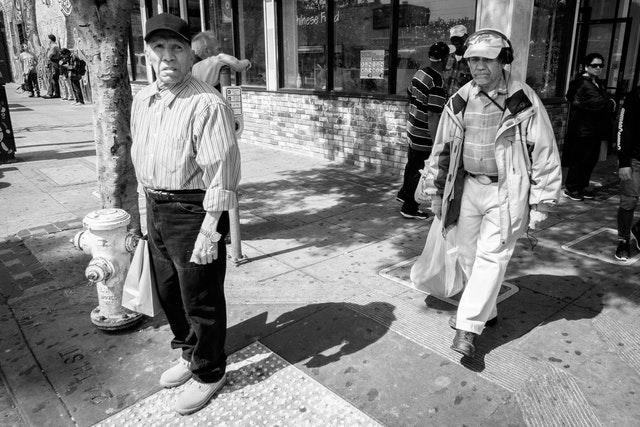A group of men on the street at 24th & Mission, San Francisco.