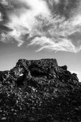 A spatter cone at Craters of the Moon, set against a sky of wispy clouds.