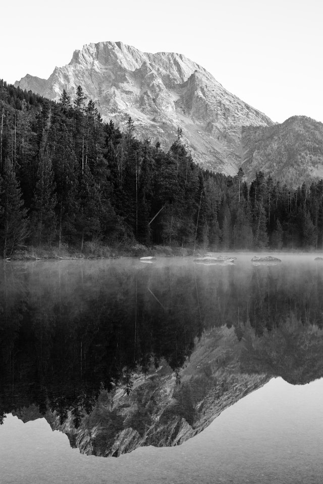 Mount Moran, reflected off the surface of String Lake at dawn. Rocks and mist can be seen on the surface of the lake.