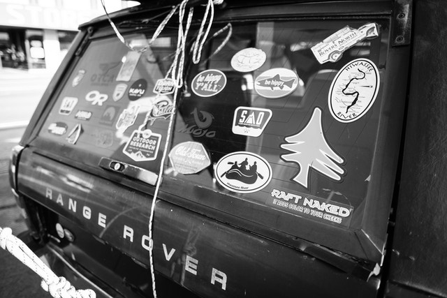 "Stickers on the back window of a Range Rover at Starr Mountain Outfitters in Etowah, Tennessee. The one in the foreground reads ""raft naked, it adds color to your cheeks""."