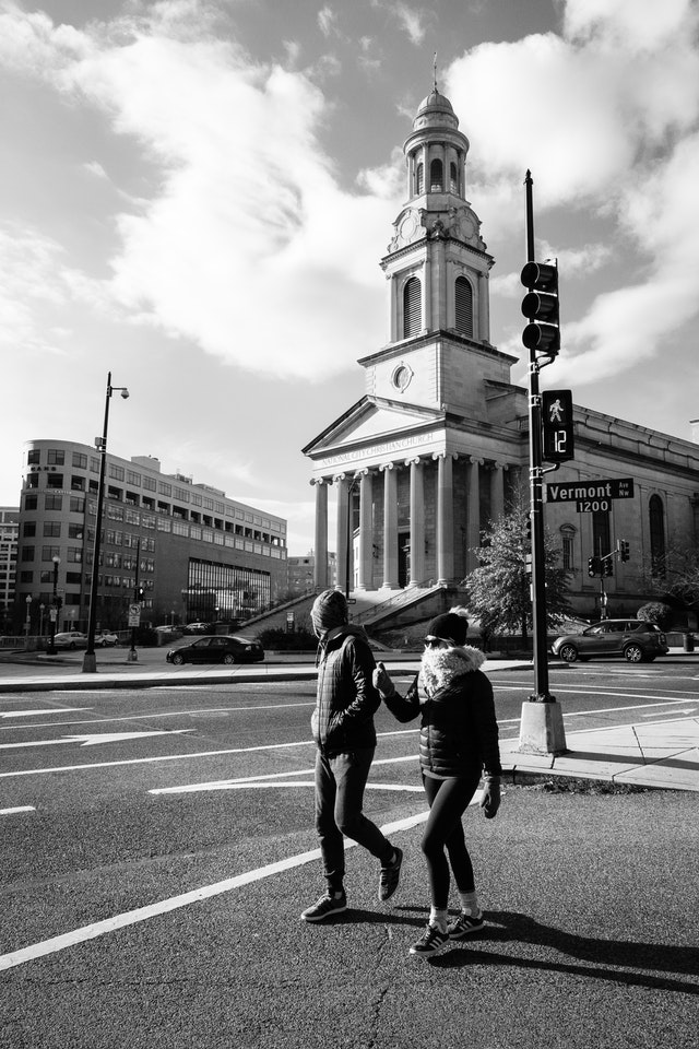 Two pedestrians walking in front of the National City Christian Church in Thomas Circle.