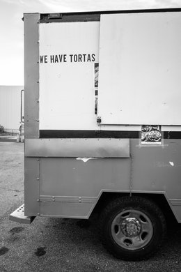 """The back of a food truck with a sign that reads """"we have tortas""""."""