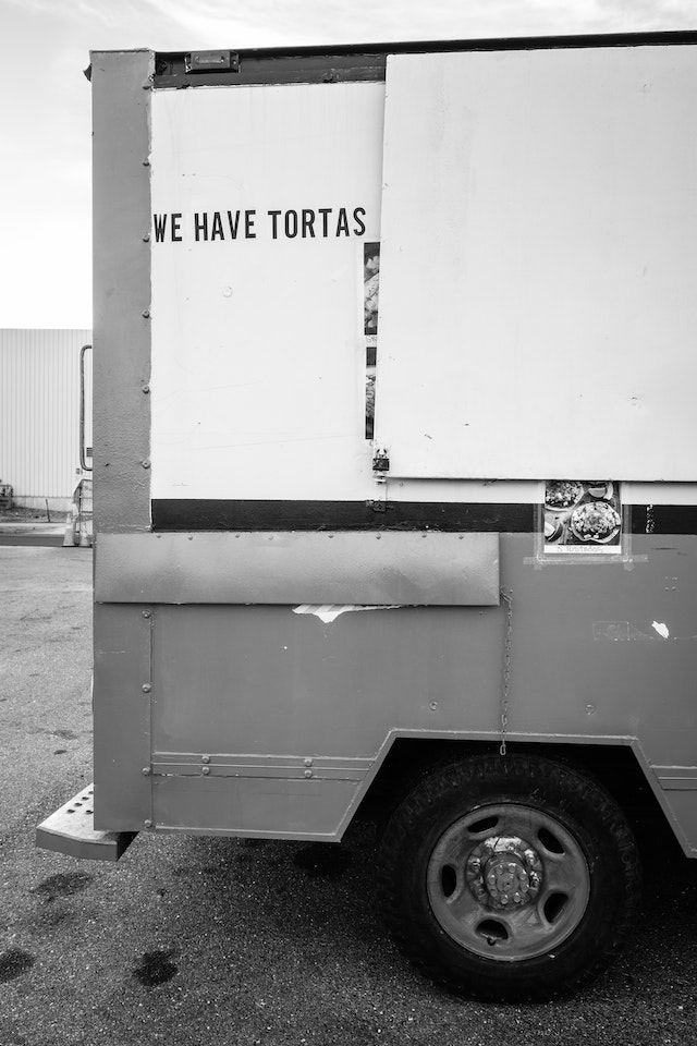 "The back of a food truck with a sign that reads ""we have tortas""."