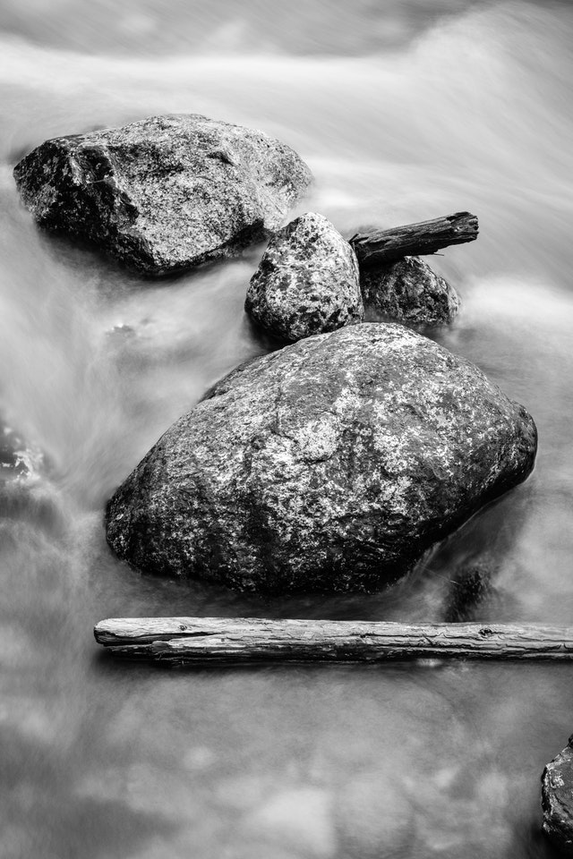A long exposure photograph of a group of boulders and driftwoof in Lake Creek, in Grand Teton National Park.