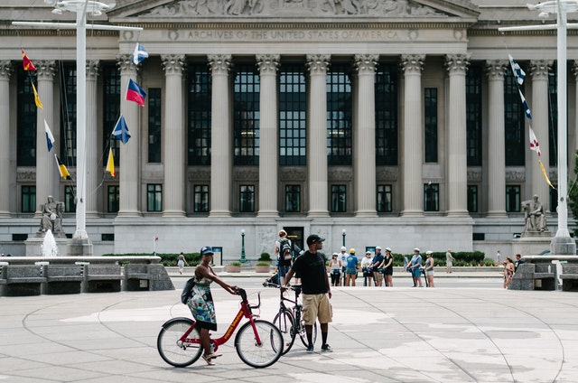 Tourists on bikes at the United States Navy Memorial in Washington, DC, with the United States National Archives in the background.