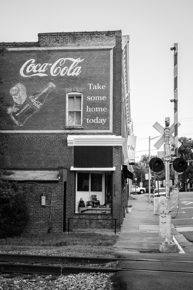 """A brick building with a vintage Coca-Cola """"take some home today"""" ad painted on its facade, in Orange, Virginia."""