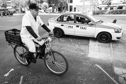A man in a white coat riding a bike next to a taxi in Mexico City.