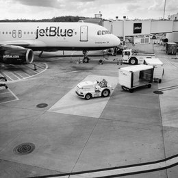 """A jetBlue Airbus A320, """"Company Blue"""", parked at a gate at Orlando International Airport."""
