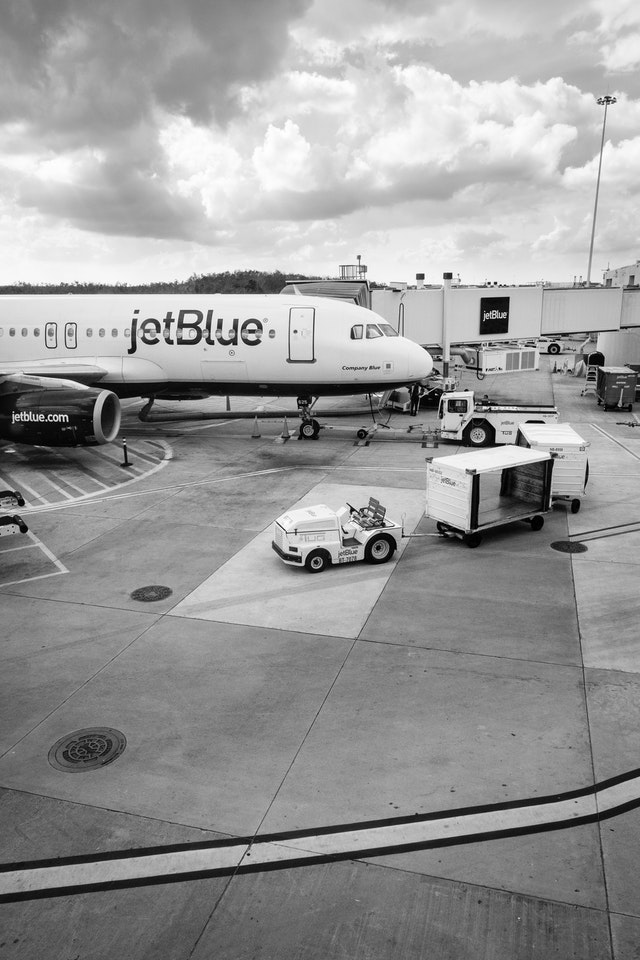 "A jetBlue Airbus A320, ""Company Blue"", parked at a gate at Orlando International Airport."