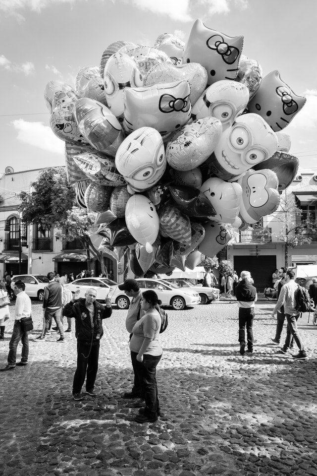 A salesman holding a bunch of balloons talking to customers.