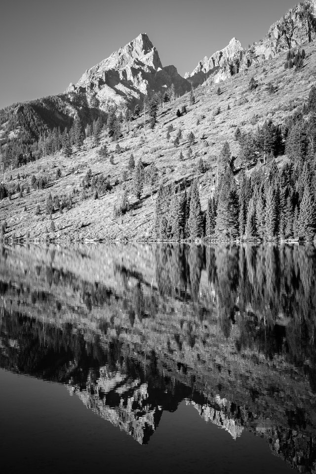 Teewinot Mountain and Grand Teton, reflected off the surface of String Lake.