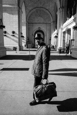 A man wearing a coat and a hat, exiting Union Station in Washington, DC.