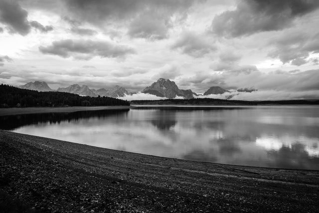 Mount Moran and the Teton Range under stormy skies at dawn. In the foreground, Jackson Lake, with its water level visibly low after a drawdown.