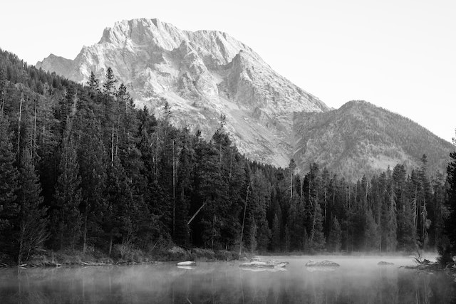 Mount Moran, seen from String Lake at dawn. Rocks and mist can be seen on the surface of the lake.